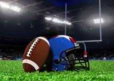 在草的橄榄球设备在体育场内 库存照片