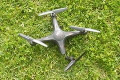 在草的残破的quadcopter 图库摄影