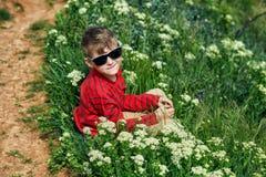在草的男孩休息的开会在国家步行期间 免版税库存照片