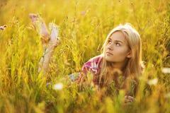在草的美丽的白肤金发的女孩 免版税图库摄影