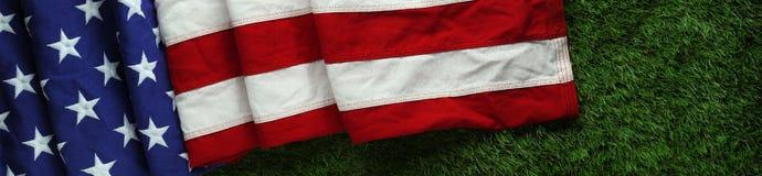 在草的美国国旗阵亡将士纪念日或退伍军人`的s天背景 库存图片