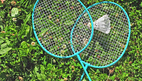 在草的羽毛球拍 库存照片