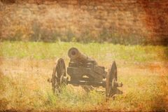 在草的老中世纪大炮在堡垒墙壁附近 免版税库存图片
