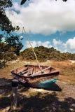 在草的老生锈的小船 免版税库存照片