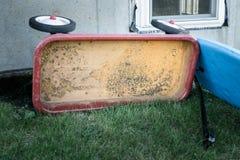 在草的老生锈的玩具无盖货车,与简单的水泥房子墙壁在背景中 库存图片