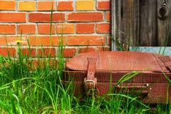 在草的老破旧的手提箱,对砖墙 免版税库存图片