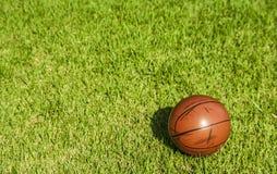 在草的肮脏的小篮球 库存照片