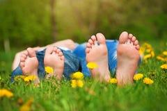 在草的脚。家庭野餐在绿色公园 免版税库存照片