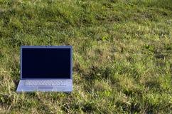 在草的膝上型计算机 免版税库存图片