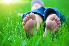 在草的英尺。 系列野餐在春天公园 免版税库存照片