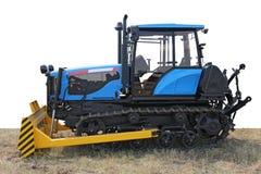 在草的蓝色大厦推土机拖拉机 库存图片