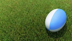 在草的蓝色橄榄球球 库存图片