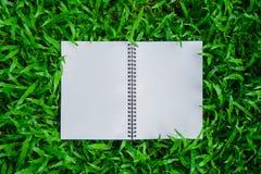 在草的被打开的白色笔记本 图库摄影