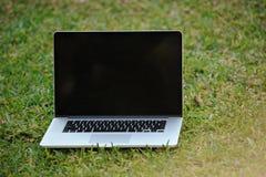 在草的被打开的膝上型计算机 免版税图库摄影