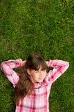在草的轻松的十几岁的女孩 生活方式、暑假和人概念 图库摄影