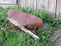 在草的边转动的古色古香的金属独轮车 免版税图库摄影