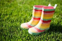 在草的镶边雨靴 免版税库存图片