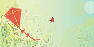 在草的风筝 免版税库存图片