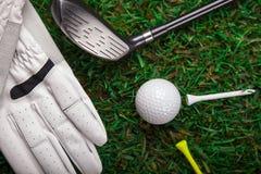 在草的高尔夫球、手套和棒! 免版税库存照片
