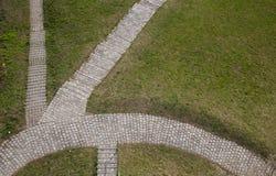 在草的鹅卵石道路 免版税库存照片