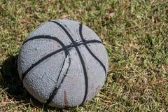 在草的破旧的篮球 免版税库存照片