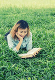 在草的年轻美丽的行家妇女阅读书 免版税库存图片
