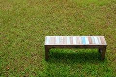 在草皮的老长木凳 库存图片