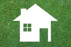 在草纹理背景, Eco建筑学的白色房子象 库存图片