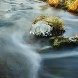 在草老黄色茎的冰柱在山河小河的冰砾增长。与被弄脏的泡影的小小瀑布。 免版税库存照片