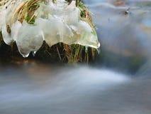 在草老黄色茎的冰柱在山河小河的冰砾增长。与被弄脏的泡影的小小瀑布。 库存照片