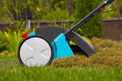 在草草坪的花匠运行的土壤通风机器 免版税库存照片
