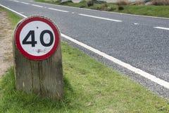 在草边缘的限速标志由路的边 免版税库存照片