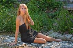 在草附近的美丽的少妇 免版税库存照片