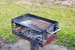 在草附近的肮脏的生锈的烤肉格栅 免版税图库摄影