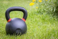 在草-后院健身的Kettlebell 免版税图库摄影