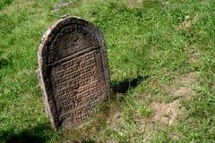 在草(坟墓)放弃的老犹太墓碑 免版税库存图片