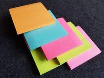 在荧光染料、背景和纹理堆积的笔记的纸笔记本 图库摄影