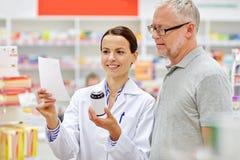 在药房的药剂师和老人买的药物 免版税库存照片