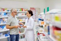 在药房的药剂师和老人买的药物 库存照片