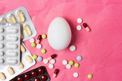 在药片和医学一个医疗背景的鸡蛋在组装 免版税库存照片