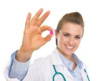 在药片的特写镜头在手中愉快的医生妇女 免版税图库摄影