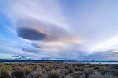 在莫诺湖的奇怪的云彩有距离的山脉的山在日出 免版税图库摄影