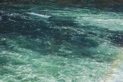 在莱茵河的小船在莱茵瀑布下 图库摄影