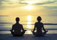 年轻在莲花坐的夫妇实践的瑜伽在日落期间的海洋海滩 免版税库存图片