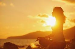 在莲花坐的孕妇实践的瑜伽在海滩在太阳 免版税库存照片