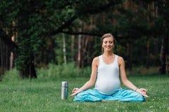 在莲花坐的怀孕的瑜伽与热水瓶 在草的,室外,健康妇女公园,女性 免版税库存照片
