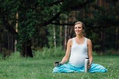 在莲花坐的怀孕的瑜伽与热水瓶 在草的,室外,健康妇女公园,女性 库存照片