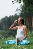在莲花坐的怀孕的瑜伽用热水瓶饮用的茶 在草的,室外,健康妇女公园,女性 库存照片