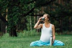 在莲花坐的怀孕的瑜伽用热水瓶饮用的茶 在草的,室外,健康妇女公园,女性 免版税库存照片