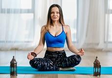在莲花姿势的瑜伽教练员 免版税库存照片